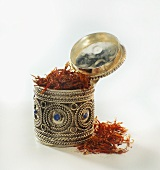 Saffron threads in a silver box and beside it