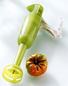 Green electric hand blender and a tomato