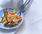 Lentil casserole with shrimps and apples on blue plate