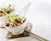 Asian chicken and sprout stir-fry in white bowl
