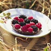 Berry tartlet on a plate on wicker tray