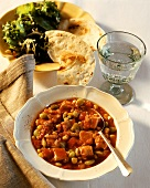 Turkey and bean stew on plates; Mineral water; Bread; Salad