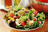 Green salad with ham on plate; oil and vinegar; tomatoes