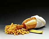 Hot dog with napkin, chips, ketchup and gherkin
