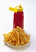 Chips on plate in front of a bottle of ketchup