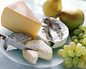 Various types of cheese with pears, grapes and knife