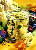 Courgettes and cauliflower in vinegar in pickling jar