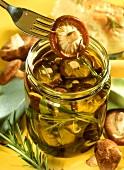 Shiitake mushrooms in rosemary oil in glass & on fork