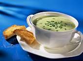 Cream of leek soup with snipped chives in soup plate