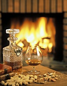 Brandy in glass and carafe on table in front of fire