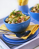 Potato salad with onions in a blue bowl