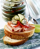 Open white bread sandwich with ham and gherkins