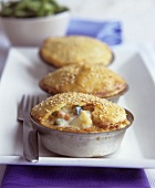 Small vegetables pies with sesame in the baking tins