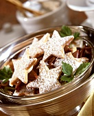 Star-shaped biscuits with icing sugar in metal bowl