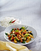 Chicken with vegetables & cashew kernels on plate; rice