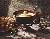 Cheese fondue with bread cubes and schnapps