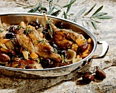 Rabbit with olives and rosemary in roasting dish