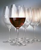 Ein halb gefülltes Rotweinglas vor leeren Rotweingläsern