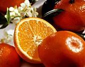 Mandarins, one halved, with blossom