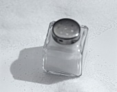 Salt in a salt cellar and on a white background
