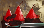 Three poached pears in red wine in chocolate coating