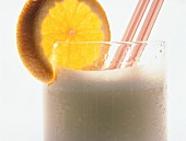 Milkshake with orange slice and drinking straw