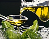 Pouring olive oil on to salad over a spoon