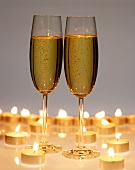Two champagne glasses surrounded by tea candles