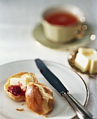 Brioche with butter and jam; Tea cup; Knobs of butter