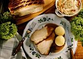 Roast pork with potato dumplings and cabbage salad