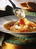 Gemüsesuppe mit Garnelen, darüber saure Sahne auf Löffel