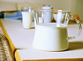 Milk in glass jug and glasses on table