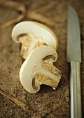 Two slices of mushroom, knife beside them