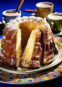 Stracciatella gugelhupf with icing sugar; cocoa cups