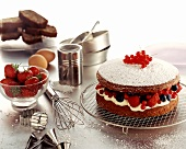 Chocolate cake with cream & berry filling; baking utensils