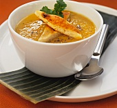 Pumpkin soup with focaccia bread in a white bowl