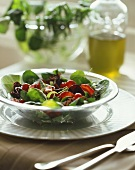 Mixed salad with strawberries on glass plate