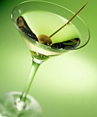 Martini with a green olive on a toothpick