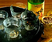 Rice wine in glasses on tray, rice wine bottle beside it