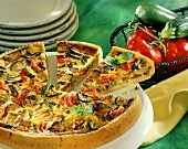 Courgette and tomato quiche on white platter