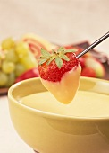 White chocolate fondue with strawberry on fondue fork