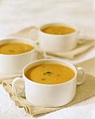 Pumpkin soup in white soup cups