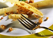 White asparagus with walnut crumbs on plate with fork