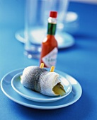 Rollmops on a plate in front of a Tabasco bottle