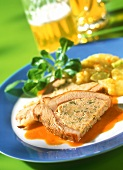 Stuffed veal breast with red wine sauce on plate; beer