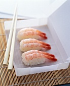 Nigiri sushi with shrimps in a white paper box