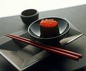 A gunkan maki with keta caviare in black bowl