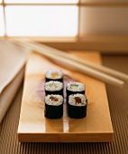 Kappa maki with cucumber & pumpkin strips on wood platter