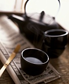 Green tea in a bowl on Japanese newspaper; teapot