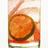 Fruit drink with slice of lime and ice cubes